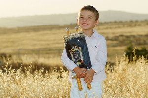 A young Jewish boy seen holding a Torah scrool as he poses for a picture in a wheat field, prior to the Jewish holiday of Shavuot. May 05, 2013. Photo by Mendy Hechtman/FLASH90 *** Local Caption *** ñôø úåøä éìã ãúé ùáåòåú